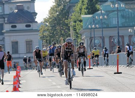 Group Of Cycling And Running Men In The Triathlon Competition
