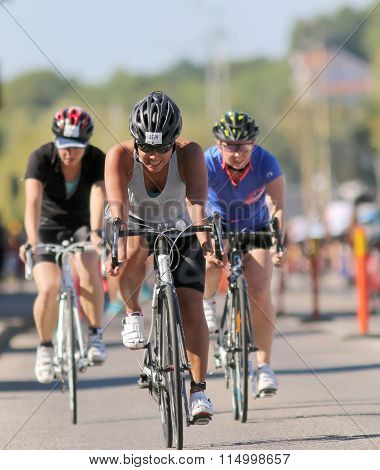 Cycling Young Woman Followed By Two Competitors