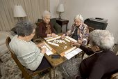 stock photo of playing card  - group of happy senior women playing mah - JPG