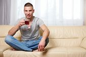 young handsome man with a cup of tea at home