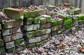 stock photo of old stone fence  - Piles of used red bricks against a wood fence - JPG