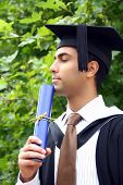 Young Indian guy in a graduation gown.
