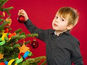 Young Boy Hanging Christmas Tree Decorations