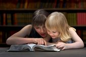 Постер, плакат: Children reading a book in the library