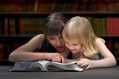 Постер, плакат: Children reading a book in the library