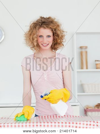 Good Looking Red-haired Woman Cleaning A Cutting Board In The Kitchen