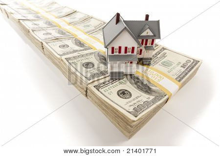 Small House on Stacks of Hundred Dollar Bills Isolated on a White Background.