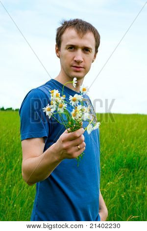 The Young Man With Camomiles On A Green Meadow