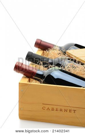 Closeup of three red wine bottles in a wooden shipping crate. The crate is partially open with excelsior packing. Vertical format over a white background with reflection.