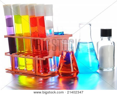 Closeup of scientific labratory equipment on shiny metal surface. Test tubes, beakers and vials filled with colorful liquids on a white background.