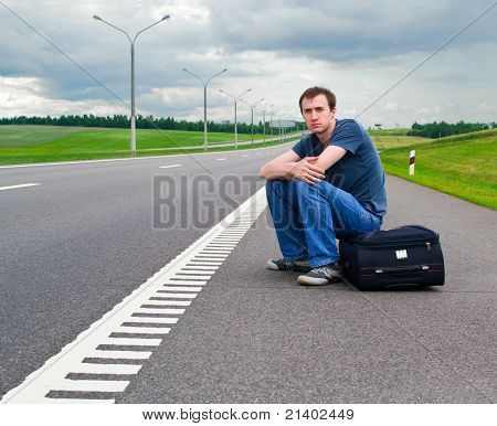 The Young Man Sits Pending On Road With A Suitcase