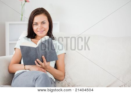 Cute Dark-haired Woman Holding A Book While Looking At The Camera