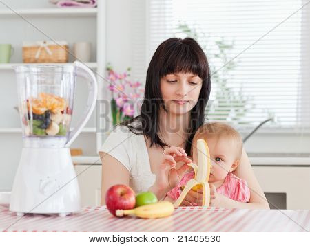 Cute Brunette Woman Pealing A Banana While Holding Her Baby On Her Knees