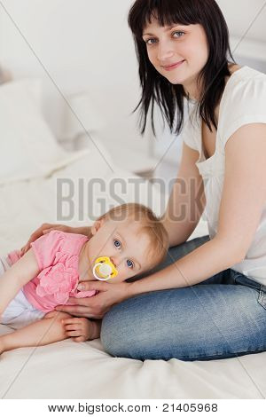 Attractive Brunette Female Posing With Her Baby Lying On Her