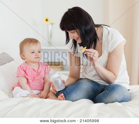 Charming Brunette Female Showing A Feeding Bottle To Her Baby While Sitting On A Bed
