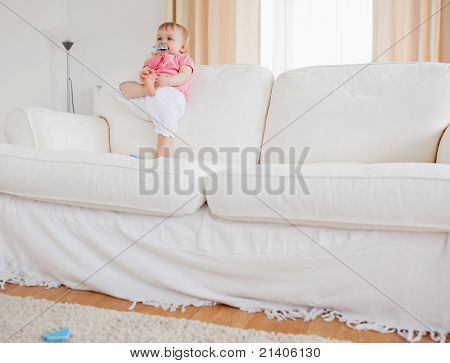 Lovely Blond Baby Playing With Puzzle Pieces While Standing On A Sofa