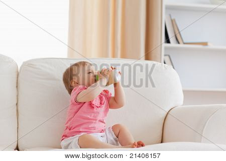 Cute Blond Baby Bottle-feeding While Sitting On A Sofa