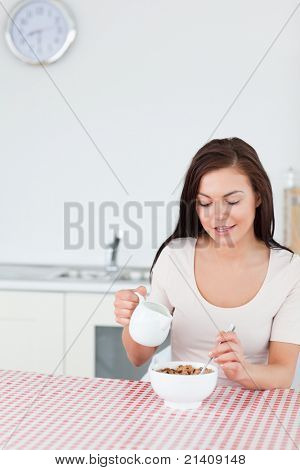 Portrait of a smiling woman pouring milk in her cereal in her kitchen