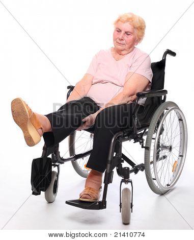 Parapléjico anciana sentada en una silla de ruedas en un blanco.