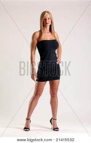 Tiny black dress on a tone blond hair woman wearing stilettos.