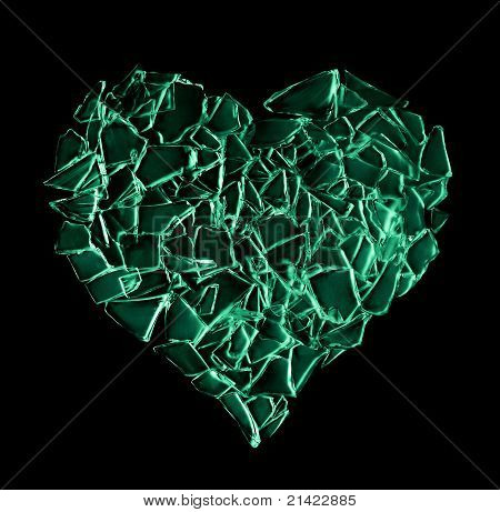 broken green glass heart isolated on black background