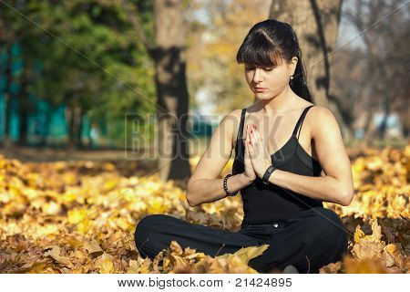Outdoor Portrait of Beautiful Young Woman Practicing Yoga in Nature