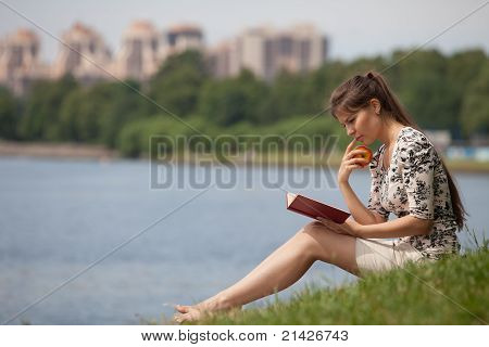 Young Woman With The Book In The Park.
