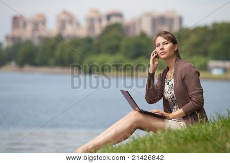 Young Woman With Laptop And Mobile Phone In The Park.
