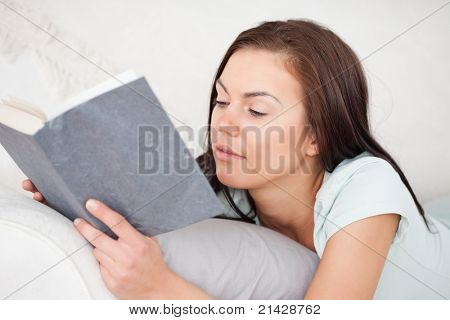 Close up of a woman on a sofa reading a book against a white background