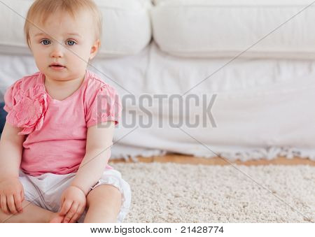 Lovely blond baby looking at the camera while sitting on a carpet in the living room