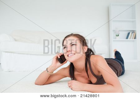 Cute young woman calling in her living room