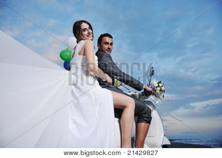 wedding scene of bride and groom just married couple on the beach ride white scooter and have fun