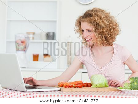 Attractive blonde woman relaxing with her laptop while cooking some vegetables in the kitchen in her apartment