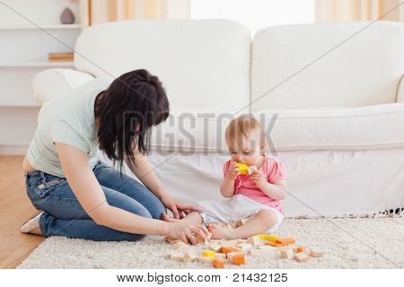 Attractive woman playing with her baby in while sitting on a carpet in the living room