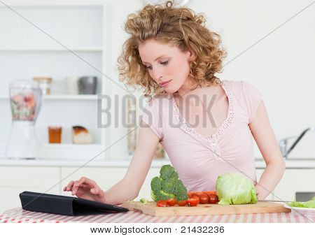 Pretty blonde woman relaxing with her tablet while cooking some vegetables in the kitchen in her apartment