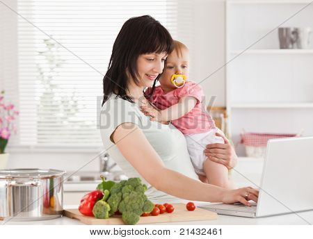 Good looking woman holding her baby in her arms while standing in the kitchen