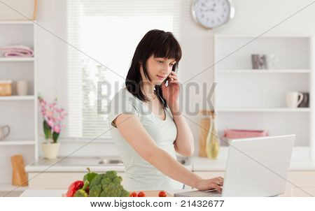 Lovely brunette woman on the phone while relaxing with her laptop in the kitchen