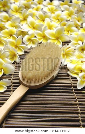 Spa brush and frangipani flower on mat