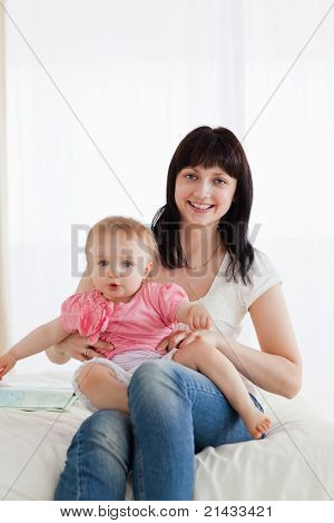 Attractive brunette woman holding her baby on her knees while sitting on a bed in her apartment