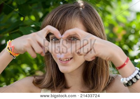 Happy Teenage Girl Forming Heart With Her Hands