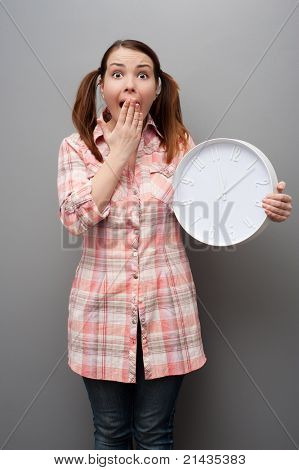 scared young woman showing wall clock over grey background