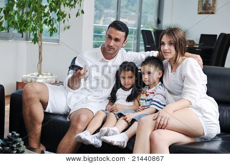 happy young family wathching flat tv at modern home indoor
