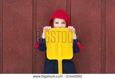 Young Boy Hides Behind Toy Shovel