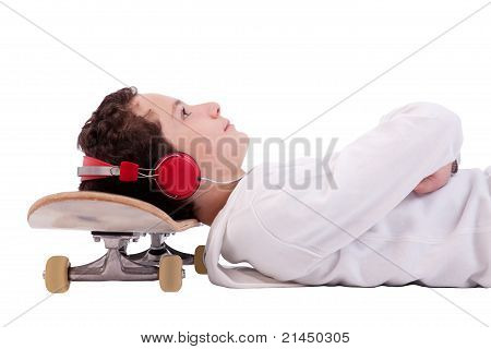 Cute Boy Lying On His Back, Listening To Music With His Head On A Skateboard, Isolated On White,stud