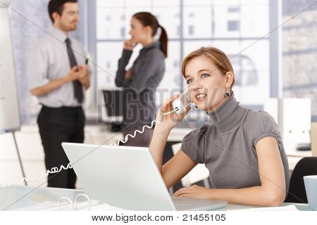 Young woman talking on phone in office, sitting at desk, using laptop, smiling, colleagues chatting in background.?