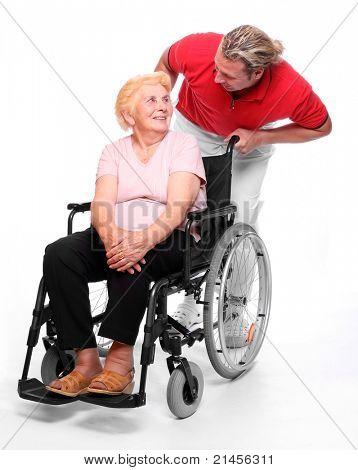 Happy elderly paraplegic woman sitting in a wheelchair and her male nurse.