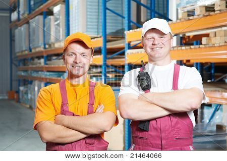 two young handsome workers man in uniform in front of warehouse rack arrangement stillages