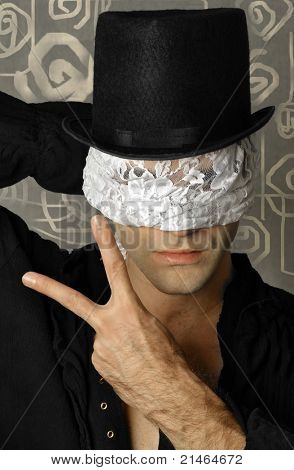 Fantastical stylized portrait of mystery man in top hat with lace blindfold making hand gesture