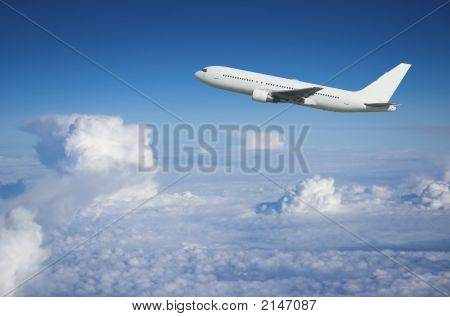 Airliner Climbing Above The Clouds