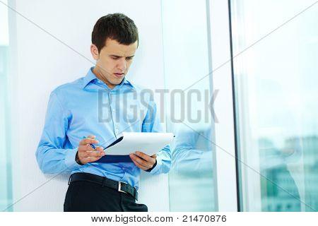 Retrato de hombre serio, mirando su plan en la oficina